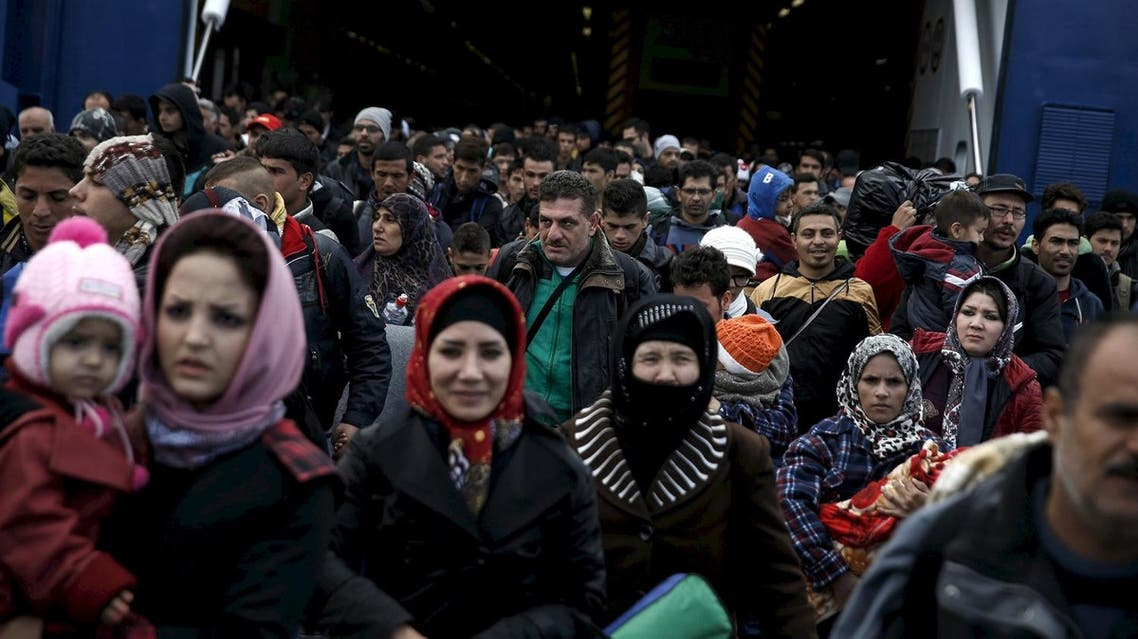 Refugees and migrants arrive aboard the passenger ferry Blue Star Patmos from the island of Lesbos at the port of Piraeus, near Athens, Greece, in this October 29, 2015 file photo. European Union leaders meet on March 7, 2016 to debate how to end the migrant crisis before a second summer of chaos, but they have already long known the available answers -- and why they have yet to add up to a solution. REUTERS