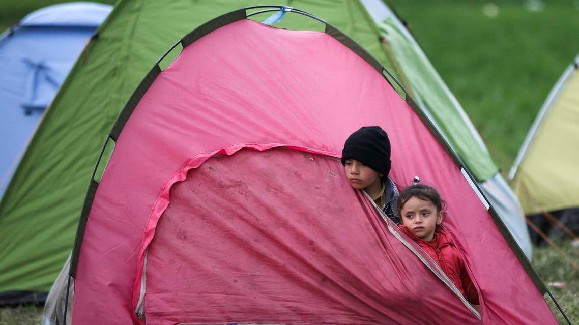 Children peer from a tent near the northern Greek border station of Idomeni, Thursday, March 3, 2016. AP