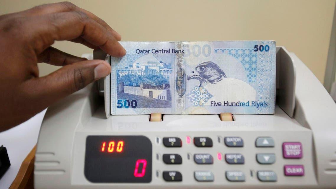 A cashier counts Qatari riyal notes at a money changer in Doha May 28, 2013. (Reuters)