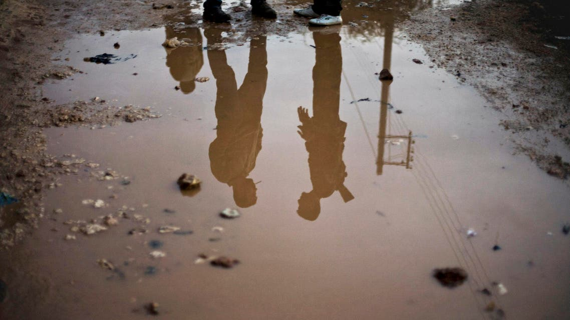 In this Wednesday, Dec. 12, 2012 photo, Free Syrian Army fighters are seen reflected in running water in the northern province of Aleppo, Syria.  (AP)
