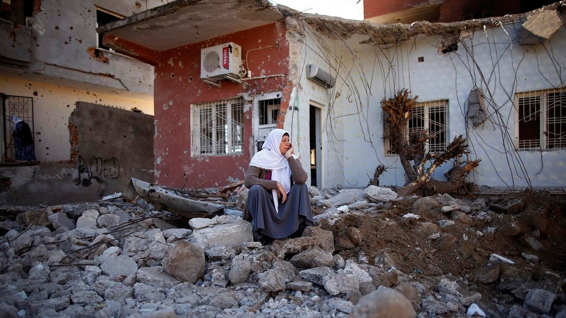 A woman looks at her ruined house in Cizre, Turkey, early Wednesday, March 2, 2016. Turkish authorities on Wednesday scaled down a 24-hour curfew imposed on the mainly Kurdish town of Cizre in southeast Turkey, nearly three weeks after declaring the successful conclusion of military operations there. AP