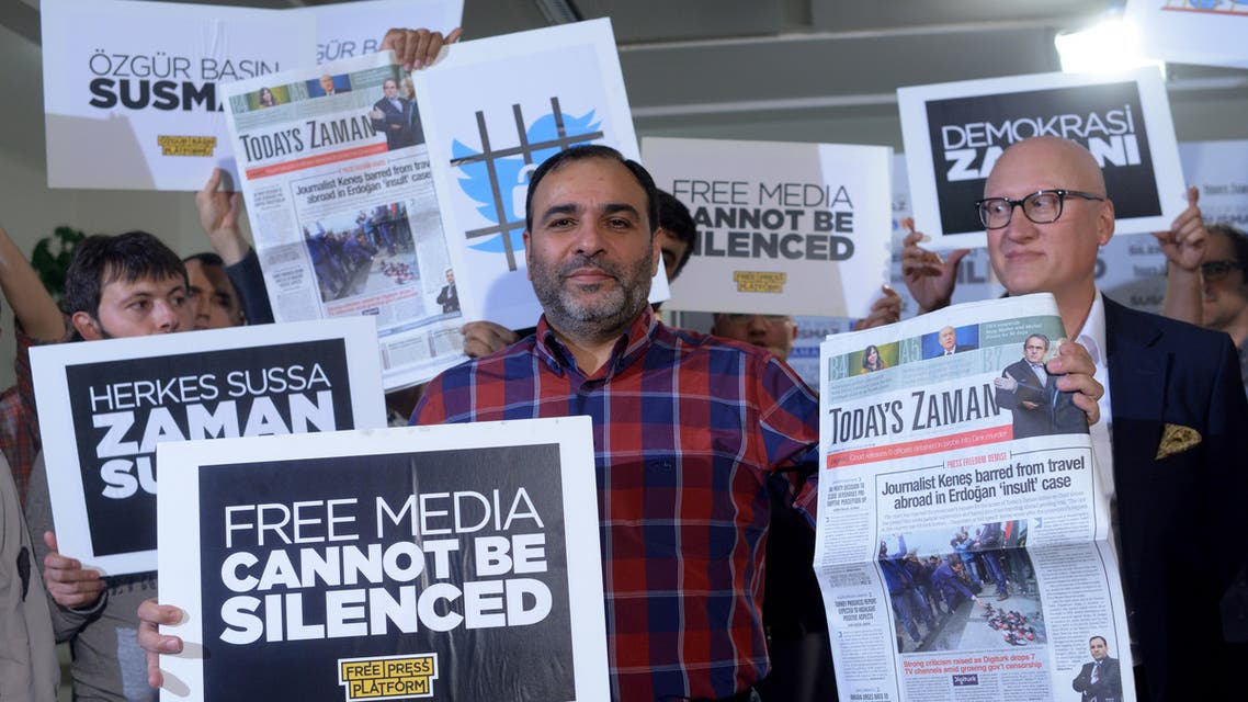 Bulent Kenes, editor-in-chief of Today's Zaman, shows his newspaper minutes before police detain him in his office in Istanbul, Turkey, late Friday, Oct. 9, 2015.