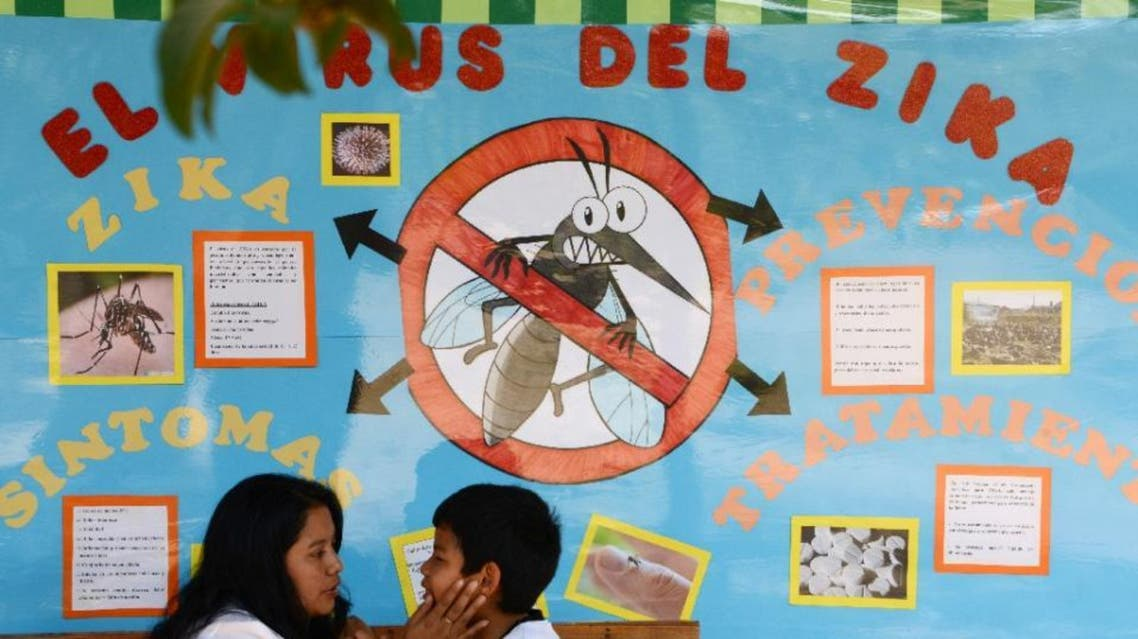 A mother and her child remain in front of a mural explaining the Zika virus in Tegucigalpa, Honduras on February 26, 2016 (AFP)