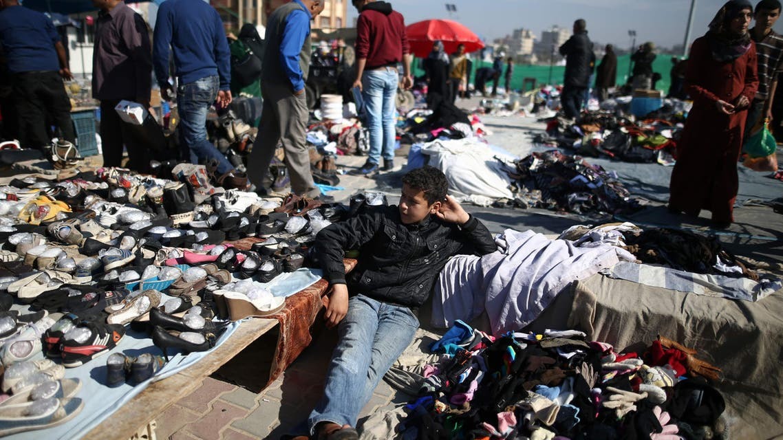 A Palestinian boy sits amidst used clothes and items at the weekly flea market in the Nusseirat refugee camp, central Gaza Strip, on February 29, 2016.  (AFP)
