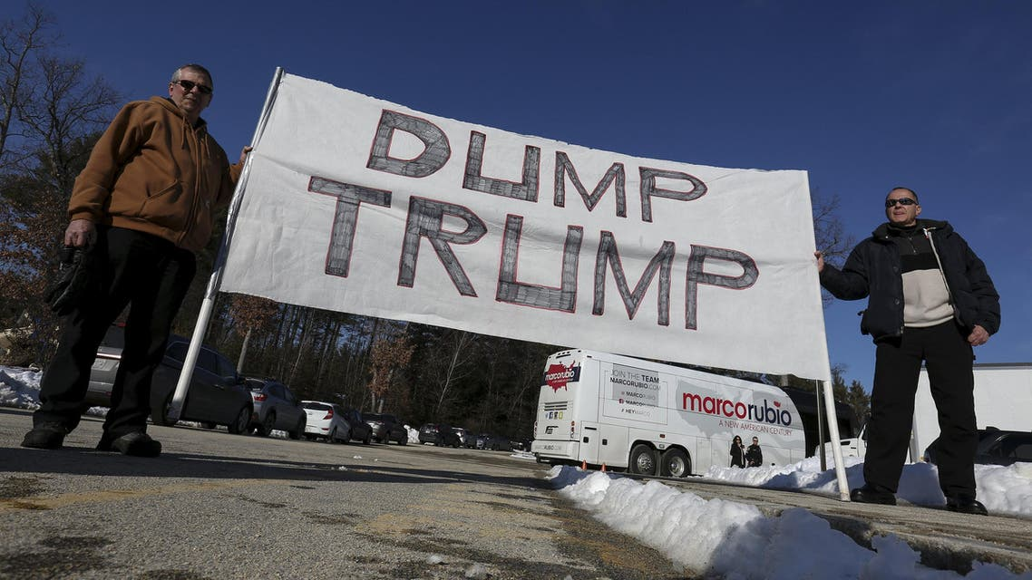 """Protesters hold up a """"Dump Trump"""" sign outside of U.S. republican presidential candidate Marco Rubio campaign event in Hudson, New Hampshire. (Reuters)"""