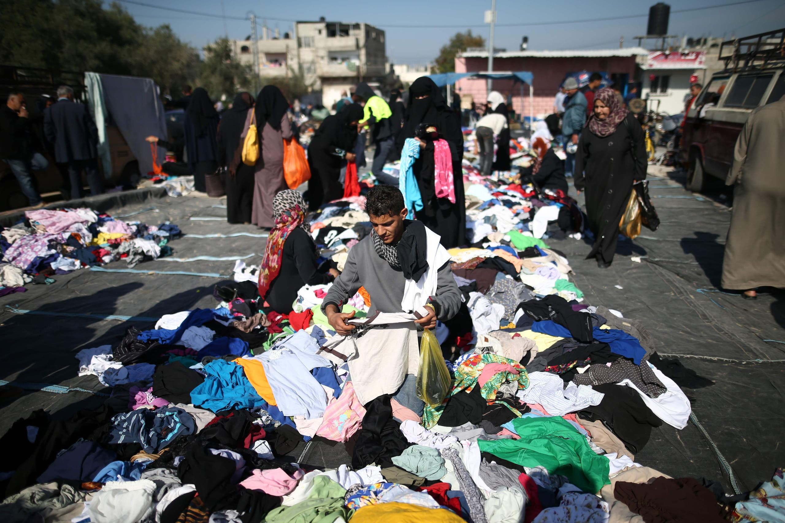 Palestinians sifts through used clothes and items at the weekly flea market in the Nusseirat refugee camp, central Gaza Strip, on February 29, 2016.(AFP)