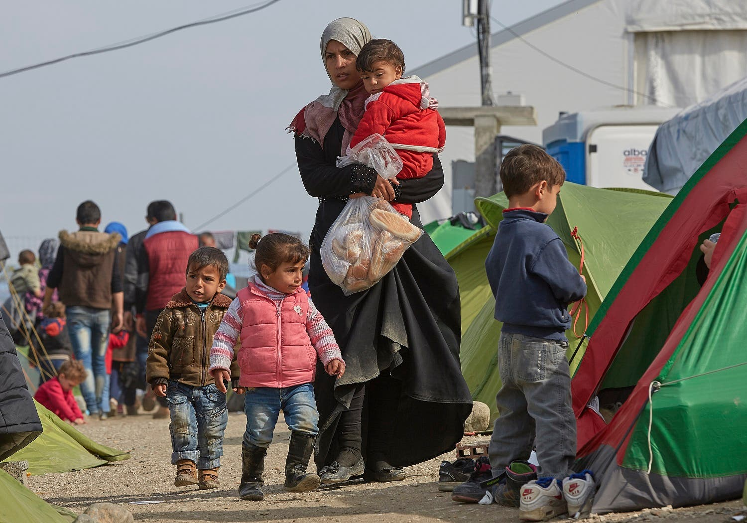 A migrant mother holds her child and a bag of bread near the border that separates the Greek side from the Macedonian one to be allowed to cross into Macedonia, at the northern Greek border station of Idomeni, Sunday, March 6, 2016. A regional governor called on the Greek government Saturday to declare a state of emergency for the area surrounding the Idomeni border crossing where thousands of migrants are stranded due to border restrictions along the route toward western Europe. (AP Photo/Visar Kryeziu)