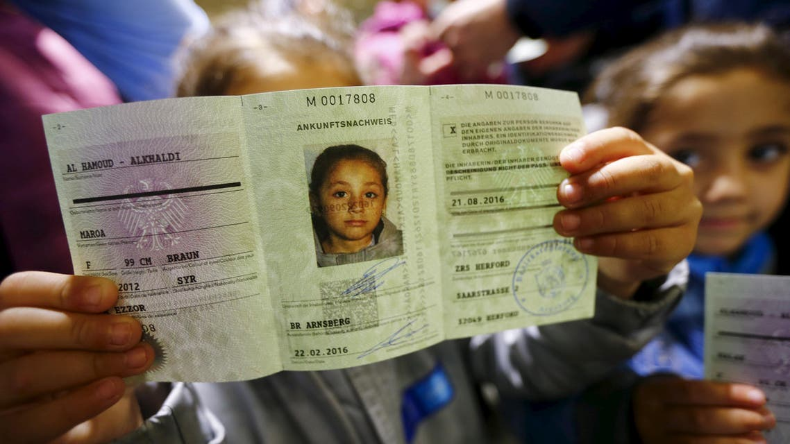 """Four-year-old Syrian girl Maroa from the eastern Syrian town of Deir ez-Zor presents her newly issued """"Ankunftsnachweis"""", an initial German registration document for migrants, following her family's registration at the former British Harewood barracks in Herford, western Germany February 22, 2016. (Reuters)"""