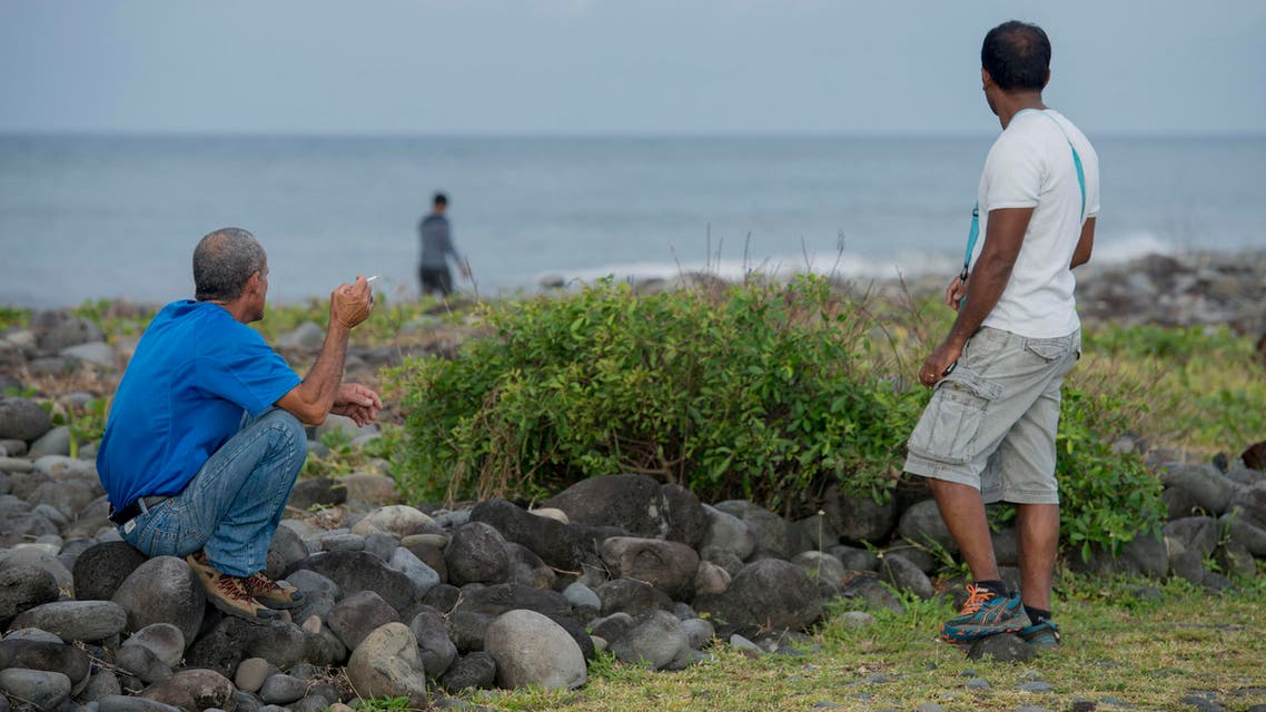 People walk on the beach of Saint-Andre, Reunion Island, in the hope of finding more plane debris, Thursday, Aug 6, 2015. AP