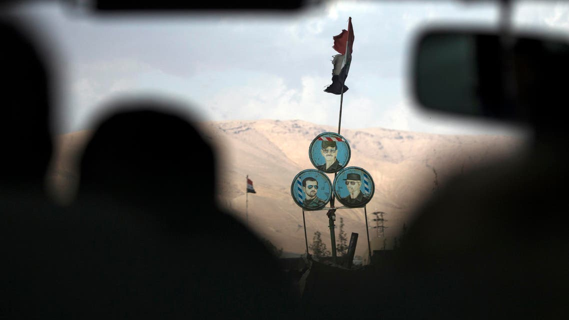 Portraits of Syrian President Bashar Assad, bottom right, Syrian general, President's Assad brother, Maher Assad, bottom left, and former Syrian President Hafez Assad, are placed at a check point on a road north of Damascus, Syria, Thursday, March 3, 2016. (AP