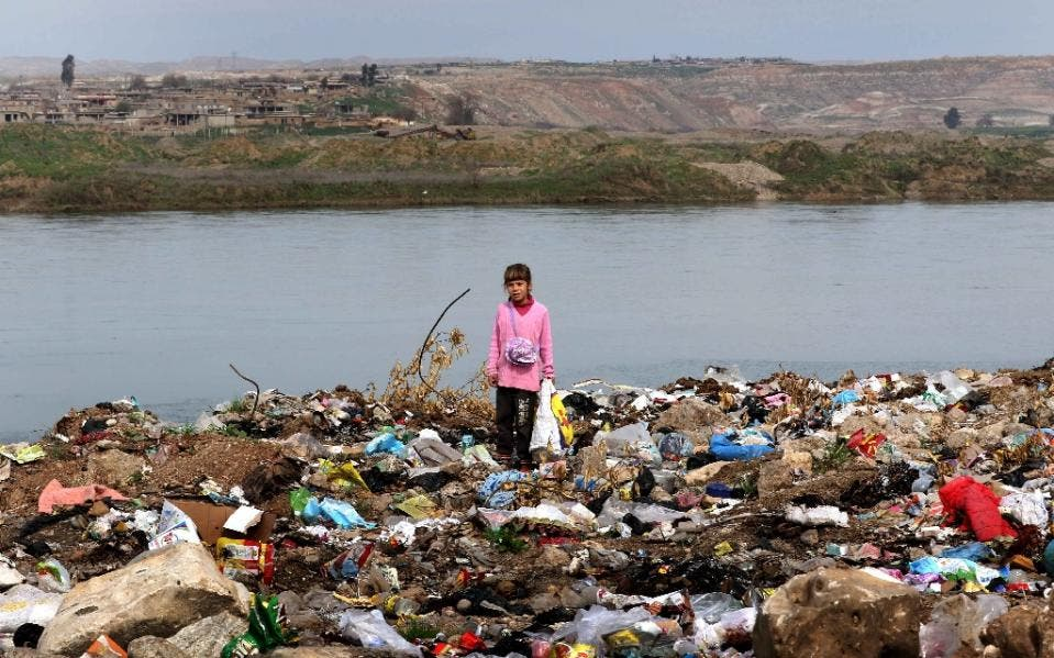 An Iraqi girl stands amid garbage on the banks of the Tigris River in the village of Wana, some 10 kms south of the Mosul Dam (AFP)