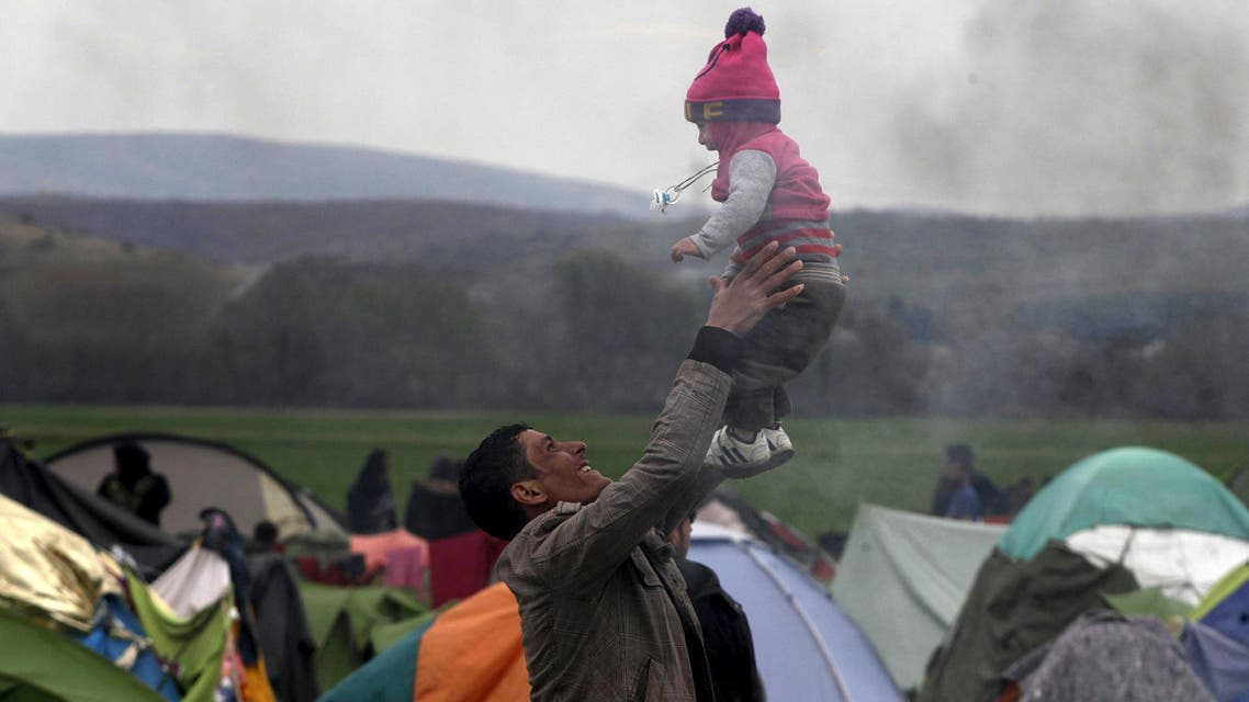 A migrant plays with a baby at a makeshift camp for refugees and migrants waiting to cross the Greek-Macedonian border, near the village of Idomeni, Greece March 6, 2016.