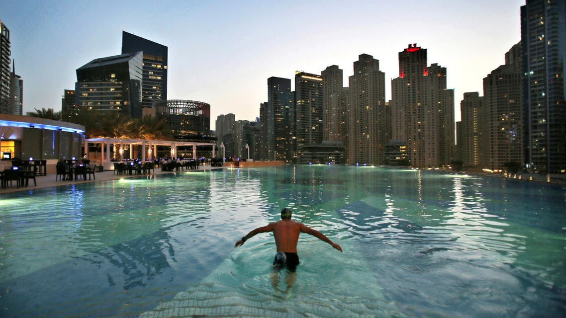 In this April 12, 2015 photo, a man dives into a hotel pool in the Marina neighborhood of Dubai, United Arab Emirates. (AP)