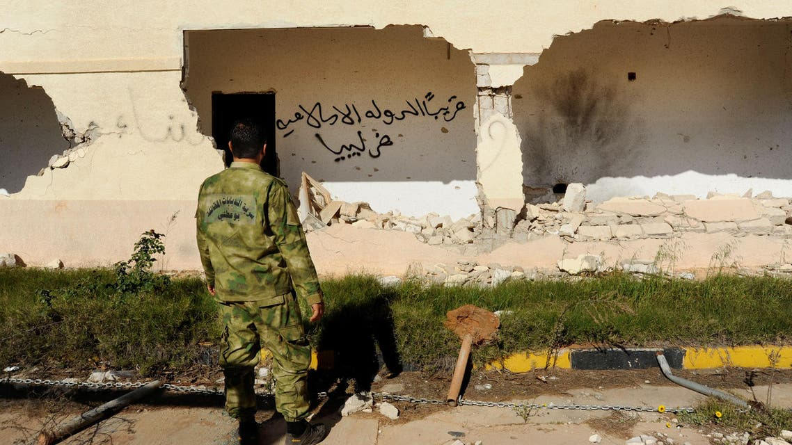 """In this picture taken Wednesday, Feb. 24, 2016, A Libyan army soldier looks at damages with Arabic that reads, """"soon, the Islamic State will be in Libya,"""" in Benghazi. AP"""