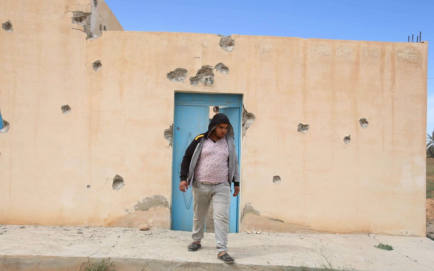 A boy stands near a bullet-riddled house, which was damaged during security operations and clashes between Tunisian security forces and ISIS in Ben Guerdan, Tunisia. (Reuters)