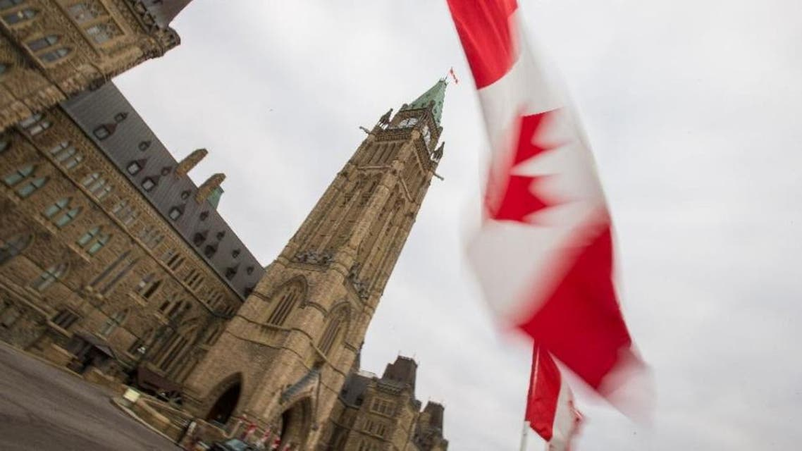 A Canadian flag flies in front of the peace tower on Parliament Hill in Ottawa, Canada on December 4, 2015 (AFP Photo/Geoff Robins)