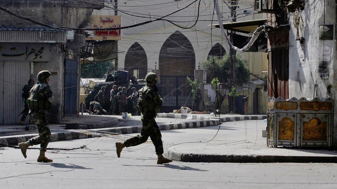 Lebanese army soldiers run during clashes with Islamic militants in the northern port city of Tripoli, Lebanon, Saturday, Oct. 25, 2014. AP