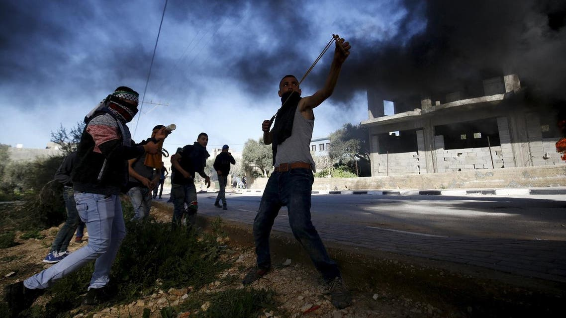 A Palestinian protester uses a slingshot to hurl stones towards Israeli troops during clashes in the West Bank village of Araka near Jenin. (Reuters)