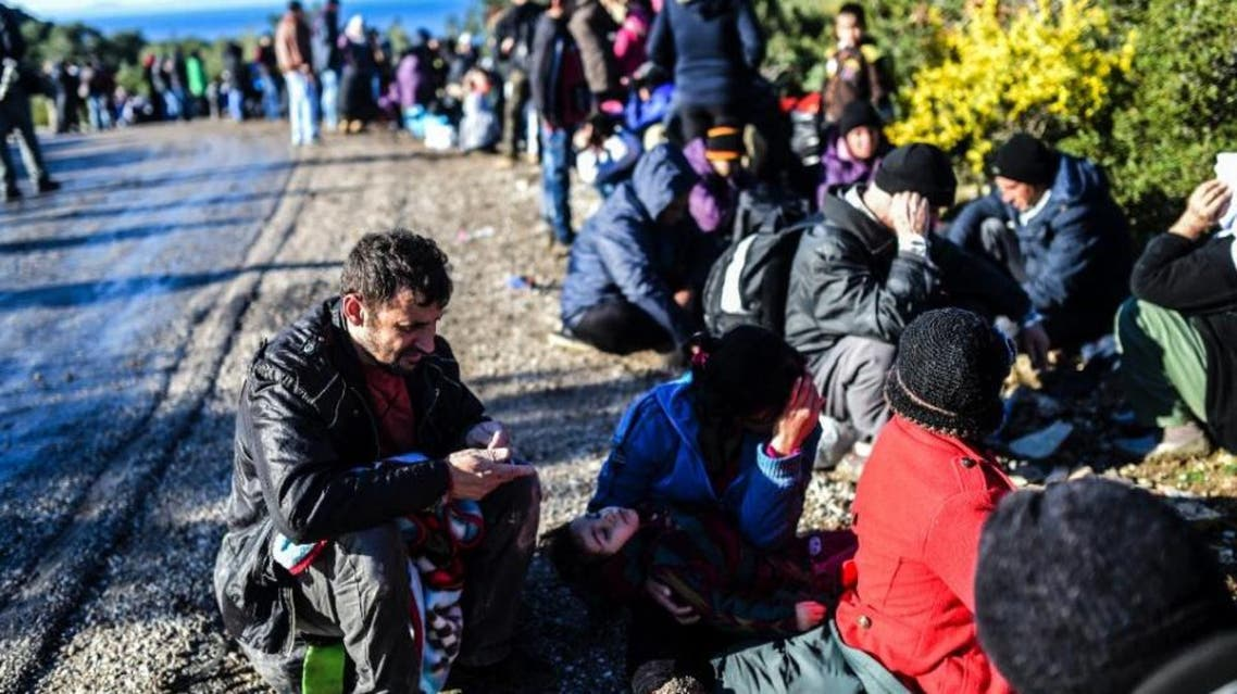 Migrants wait at the side of the road after being detained by Turkish soldiers as they try to reach the Greek island of Lesbos from Dikili, western Turkey, on March 5, 2016 (AFP)
