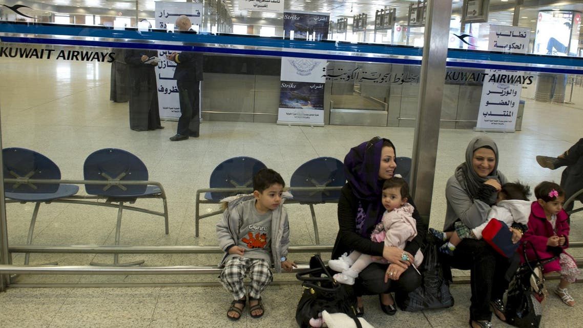 Passengers sit outside the Kuwait Airways terminal area at the Kuwait International Airport, in this March 18, 2012 file picture. (Reuters)