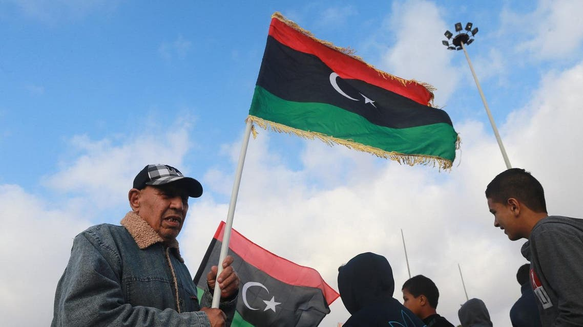 A Libyan man waves the national flags as he celebrates Libya's eastern government's gains in the area, in Benghazi, Libya reuters