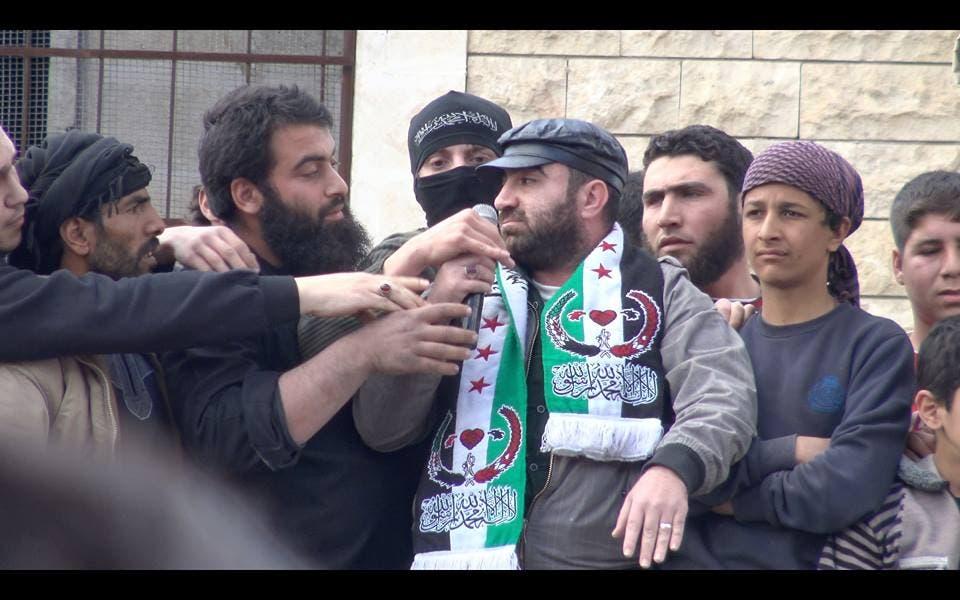 Al-Nusra militants grab at the microphone held by poet Hani Allahlah during a protest in Maarat al Noaman