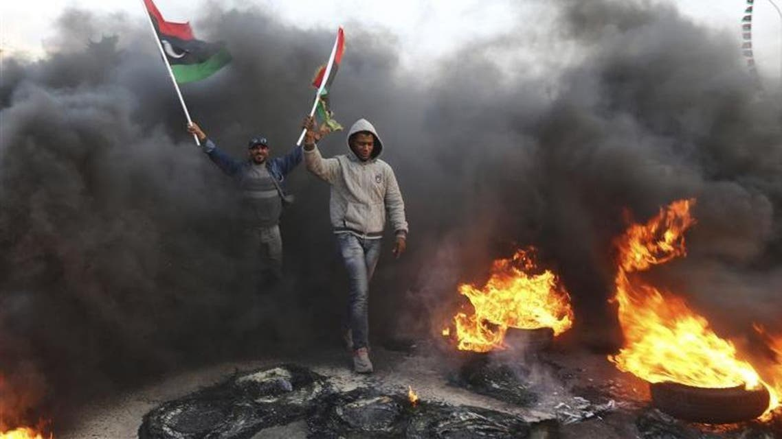 People hold Libyan flags amid smoke and fire after protesters set tyres on fire in a street during a demonstration against the General National Congress (GNC) in Benghazi February 21, 2014. (File photo: Reuters)