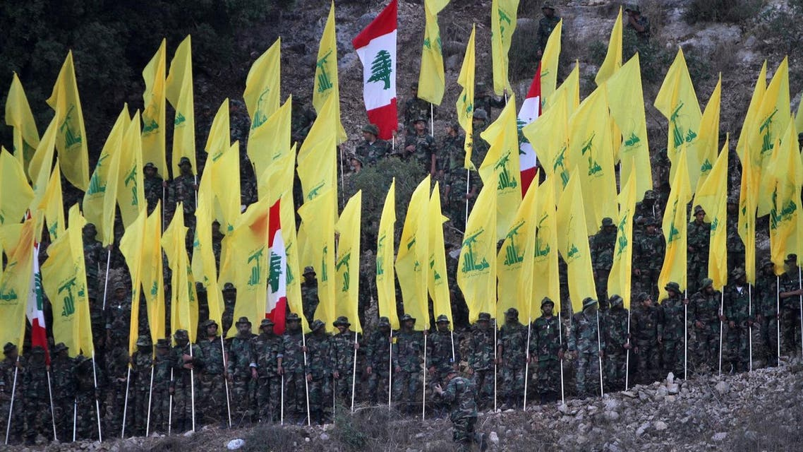 In this August 14, 2015, file photo, Hezbollah fighters hold their group and Lebanese flags, as they perform during a rally marking the ninth anniversary of the 2006 Israel-Hezbollah war, at the southern Lebanese village of Wadi al-Hujair, Lebanon. A Saudi-led bloc of six Gulf Arab nations formally branded Hezbollah a terrorist organization on Wednesday, ramping up the pressure on the Lebanese militant group fighting on the side of President Bashar Assad in Syria. (AP Photo/Mohammed Zaatari, File)
