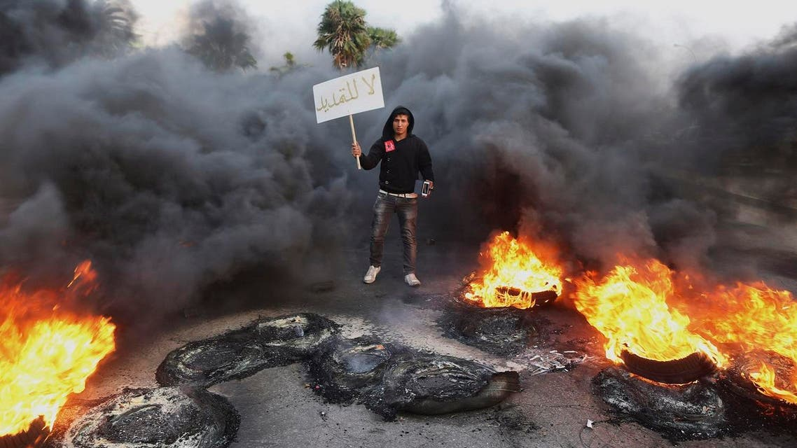 """A man holds a sign which reads, """"Not extendable"""" amid smoke and fire after angry protesters set tyres on fire in a street during a demonstration against the General National Congress (GNC) in Benghazi February 21, 2014. (File photo: Reuters)"""