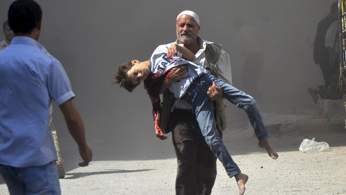 ATTENTION EDITORS - VISUAL COVERAGE OF SCENES OF INJURY OR DEATH A man carries a boy wounded in what the Free Syrian Army said was an air raid by forces loyal to Syrian President Bashar al-Assad in the Duma district area near Damascus, Syria July 13, 2013. REUTERS/Bassam Khabieh TEMPLATE OUT SEARCH 'FIVE YEARS SYRIA' FOR ALL IMAGES