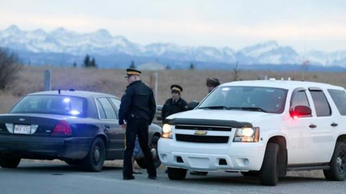 Royal Canadian Mounted Police (RCMP) officers man a road block leading to a Muslim cemetery near Cochrane, Canada, on Friday (March 11, 2016). RCMP said at least three people have been shot at the cemetery just outside of Calgary. (AP)