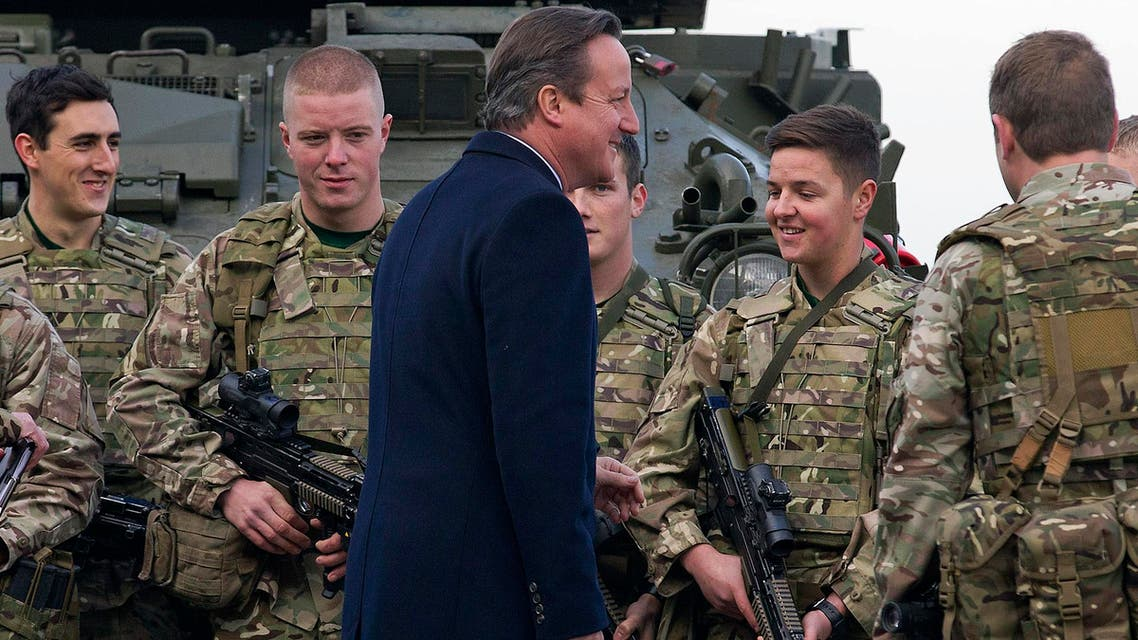 Britain's Prime Minister David Cameron (C) chats with soldiers from the Royal Welsh Infantry as they stand in front of a Lockheed Martin Warrior Infantry Fighting Vehicle, at RAF Northolt in London, Britain November 23, 2015. (Reuters)