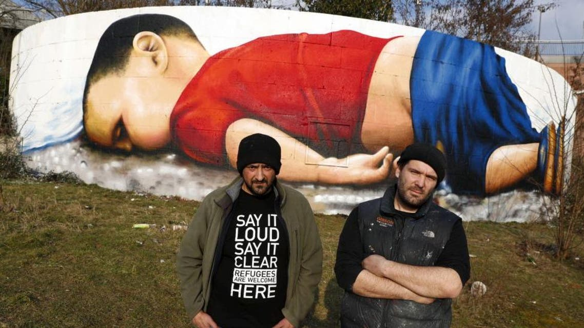 Artists Justus Becker (R) and Oguz Sen stand in front of a huge graffiti artwork of Syrian toddler Aylan Kurdi, after finishing a three-day painting session on a wall on the banks of river Main near the headquarters of the European Central Bank in Frankfurt, Germany, March 10, 2016. (Reuters)