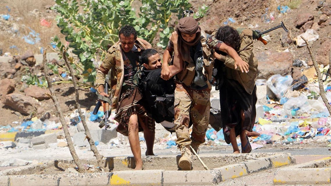 Fighters from local resistance units carry a fellow fighter who was injured in clashes between local fighters and Shiite rebels known as Houthis, in Taiz, Yemen, Friday, March 11, 2016. Yemeni medical officials say clashes between Shiite rebels and local fighters in the besieged city of Taiz have intensified, killing several dozen people on both sides over the past 24 hours. (AP Photo/Abdulnasser Alseddik)