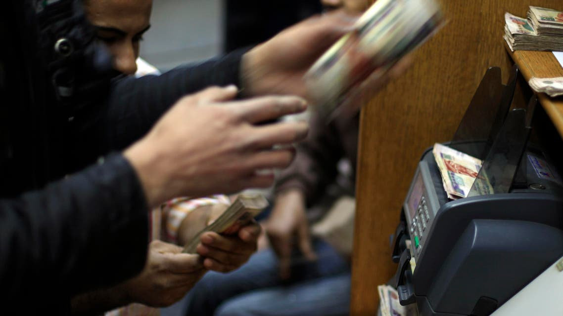 Egyptians count money at a currency exchange office in downtown Cairo, Egypt (AP)