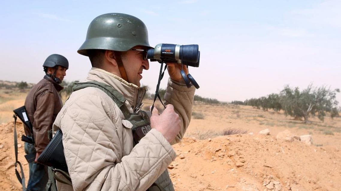 A policemen looks through a binocular during a military operation to eliminate militants in a village some 50 km (31 miles) from the town of Ben Guerdane, Tunisia, near the Libyan border, March 10, 2016 (Reuters)