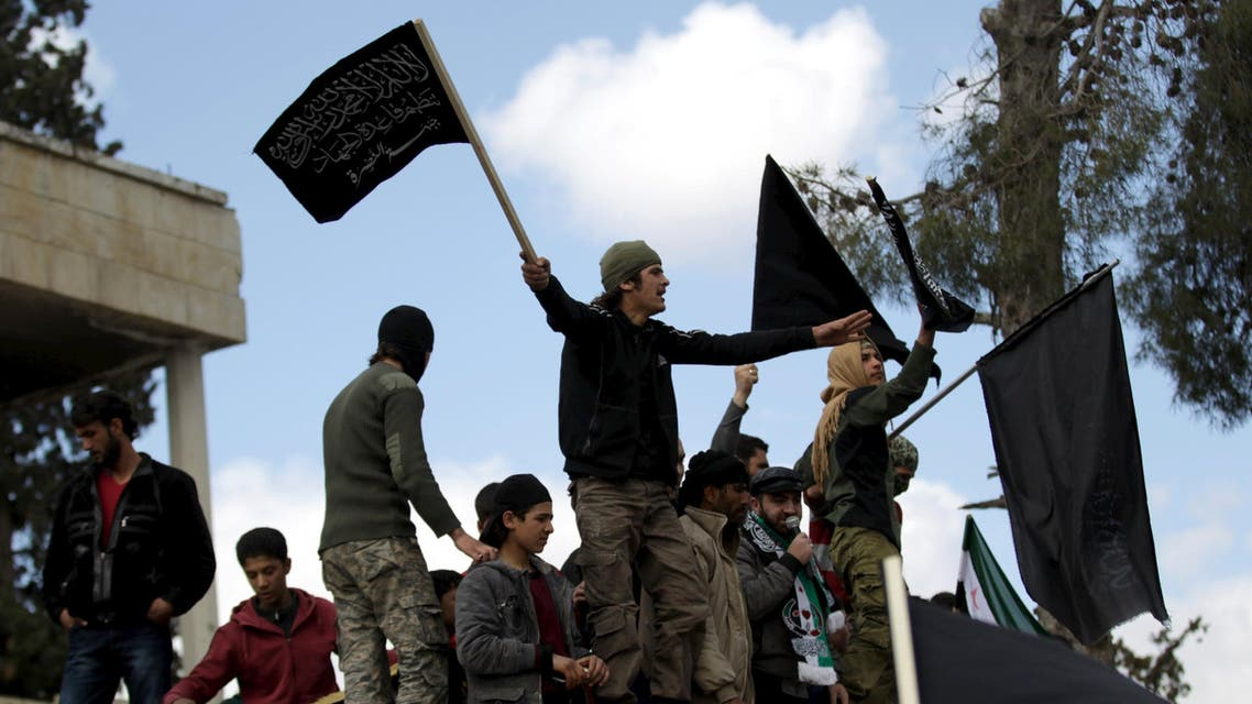 Protesters carry Nusra Front flags and shout slogans during an anti-government protest after Friday prayers in the town of Marat Numan in Idlib province, Syria, March 11, 2016. (Reuters)