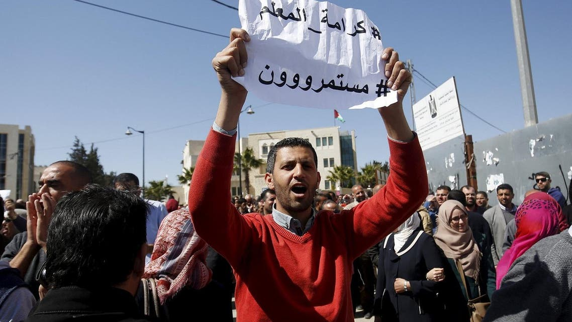 """A Palestinian teacher holds a sign that reads """"Teacher's dignity, we will continue"""" during a protest demanding better pay and conditions, in the West Bank city of Ramallah March 7, 2016. For a month, more than 25,000 teachers in the West Bank have been on strike over pay and benefits, causing chaos for schools, pupils and parents, and prompting the Palestinian Authority to deploy military police on the streets of Ramallah. Picture taken March 7. REUTERS/Mohamad Torokman"""