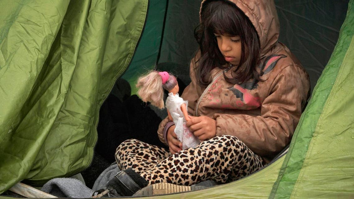 A girl holds a doll while sitting in a tent at the northern Greek border station of Idomeni, Saturday, March 12, 2016. Up to 14,000 people are stranded on the outskirts of the village of Idomeni in a makeshift camp. (AP Photo/Vadim Ghirda)