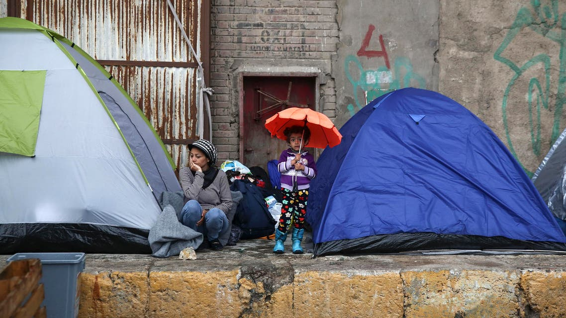 A girl holding an umbrella stands in front of tents at the Athens' port of Piraeus, on Saturday, March 12, 2016.  (AP)