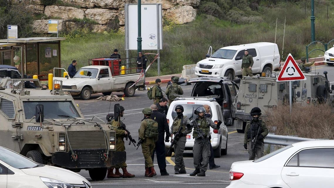 Israeli security forces gather near the scene of what the Israeli military said were back-to-back gun and car-ramming attacks by Palestinians, near the Jewish settlement of Kiryat Arba near the West Bank city of Hebron March 14, 2016. Three Palestinians carried out back-to-back gun and car-ramming attacks on Israelis near a Jewish settlement in the occupied West Bank on Monday and were shot dead by the army, it said. REUTERS