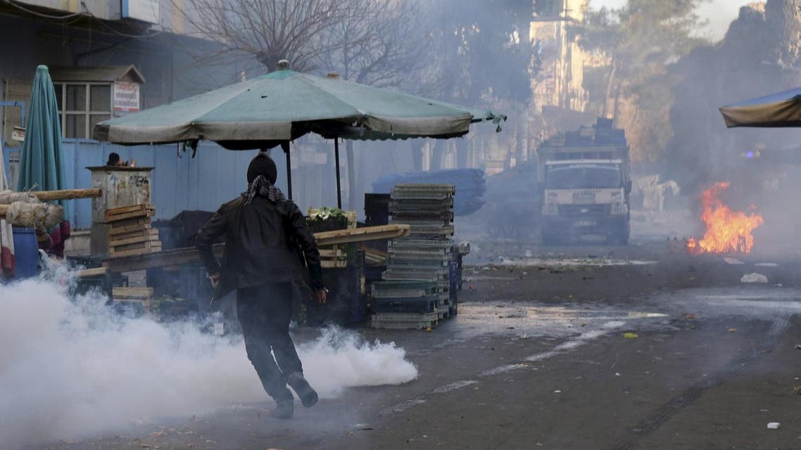 A demonstrator runs to take cover as Turkish riot police use tear gas to disperse Kurdish demonstrators during a protest against a curfew in Sur district and security operations in the region, in the southeastern city of Diyarbakir. (File photo: Reuters)