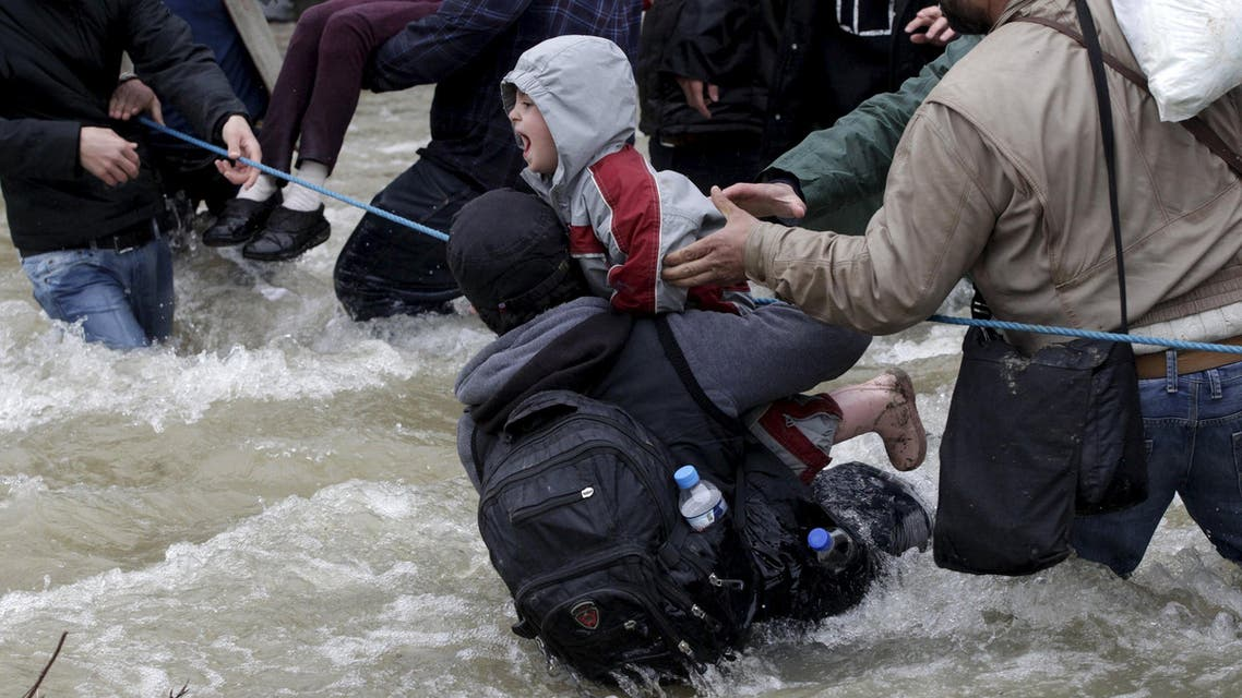 A migrant tries to stop a child from falling in the water as migrants wade across a river near the Greek-Macedonian border, west of the the village of Idomeni, Greece, March 14, 2016. REUTERS