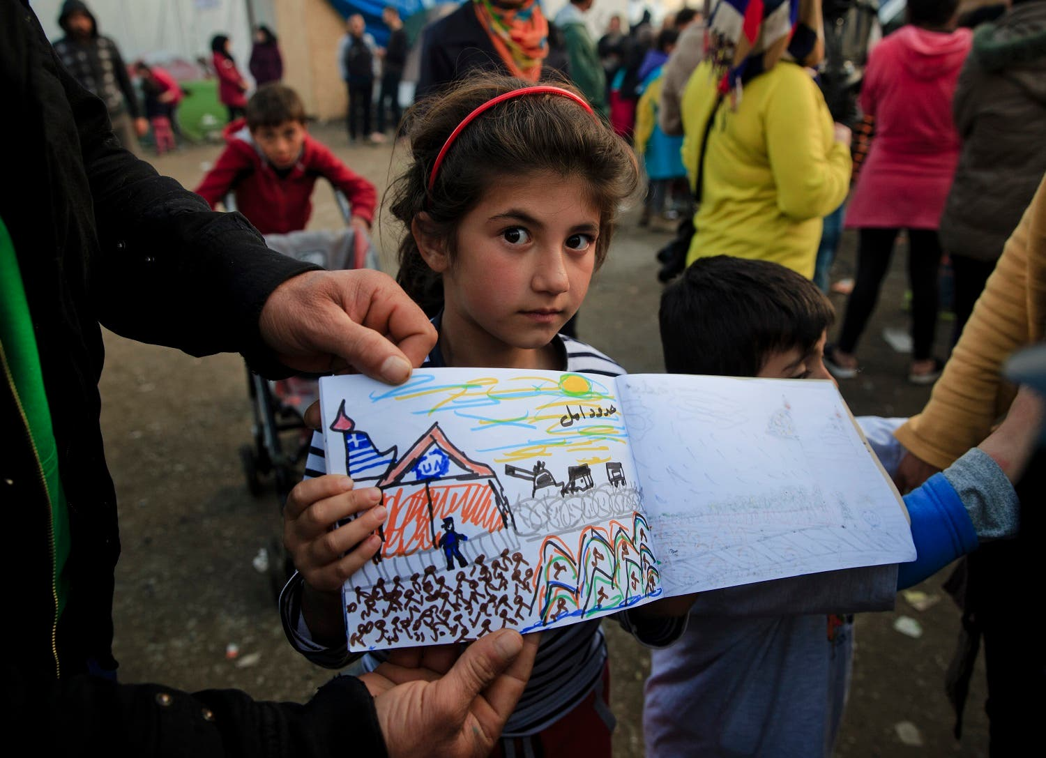 Shaharzad Hassan, 8 year-old from the Syrian city of Aleppo poses with a drawing she made at the northern Greek border station of Idomeni, Friday, March 11, 2016. At an overcrowded refugee camp on the Greek-Macedonian border, 8-year-old Shaharzad Hassan draws pictures of the harrowing events in her life over the past 18 months: Pictures of death in her home town of Aleppo, Syria, and her perilous journey to Europe. The title this drawing seen top right reads