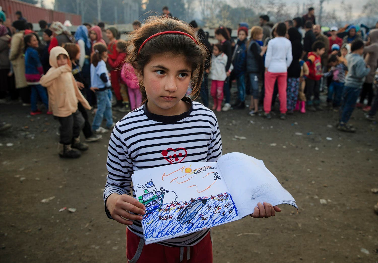 Shaharzad Hassan, 8 year-old from the Syrian city of Aleppo poses with a drawing she made, depicting a migrants rescue operation by the Greek navy, as people wait in line for food rations at the northern Greek border station of Idomeni, Friday, March 11, 2016. At an overcrowded refugee camp on the Greek-Macedonian border, 8-year-old Shaharzad Hassan draws pictures of the harrowing events in her life over the past 18 months: Pictures of death in her home town of Aleppo, Syria, and her perilous journey to Europe. (AP Photo/Vadim Ghirda)
