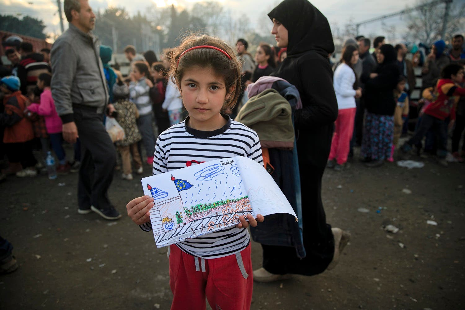 Shaharzad Hassan, 8 year-old from the Syrian city of Aleppo poses with a drawing she made as people wait in line for food rations at the northern Greek border station of Idomeni, Friday, March 11, 2016. At an overcrowded refugee camp on the Greek-Macedonian border, 8-year-old Shaharzad Hassan draws pictures of the harrowing events in her life over the past 18 months: Pictures of death in her home town of Aleppo, Syria, and her perilous journey to Europe. The title, of this drawing seen at top right reads