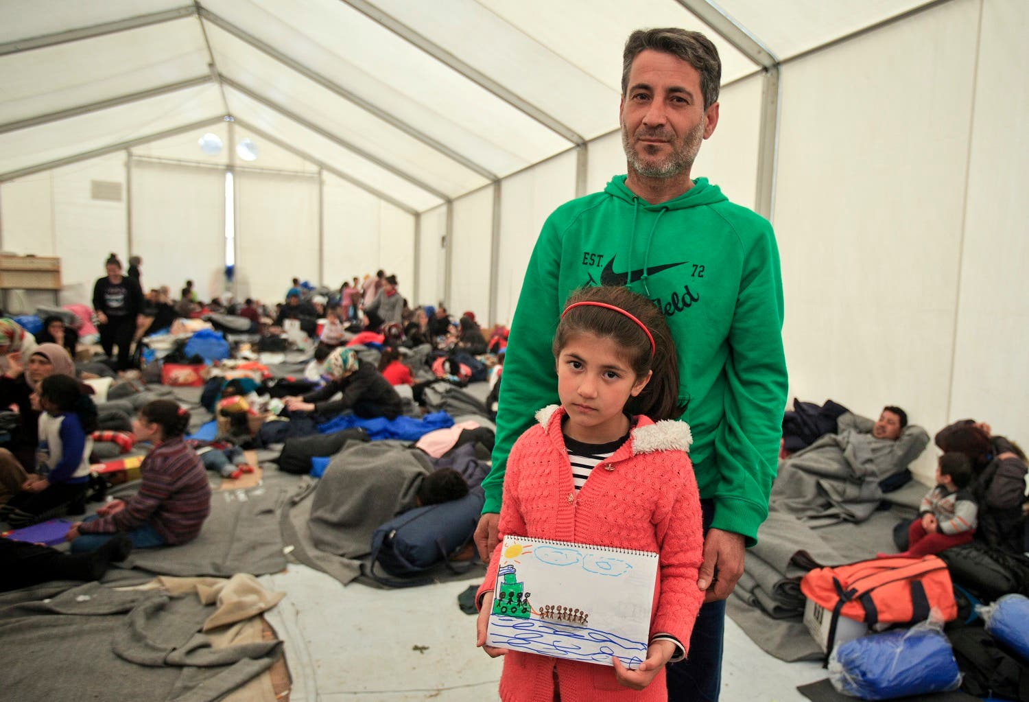 Shaharzad Hassan, 8 year-old from the Syrian city of Aleppo poses with her father Mohamed Hussein Hassan, holding a drawing she made, depicting migrants sailing in a dinghy, at the northern Greek border station of Idomeni, Friday, March 11, 2016. At an overcrowded refugee camp on the Greek-Macedonian border, 8-year-old Shaharzad Hassan draws pictures of the harrowing events in her life over the past 18 months: Pictures of death in her home town of Aleppo, Syria, and her perilous journey to Europe. The title of this drawing is