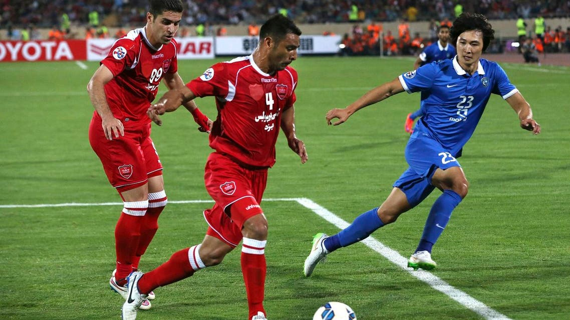 Iran's Persepolis soccer player Michael Umana, center, plays the ball as Saudi Arabia's al Hilal player Kwak Taehwi, right, and Babak Hatami of Persepolis follow, during their match in AFC Champions League at the Azadi (Freedom) stadium in Tehran, Iran. (File photo: AP)
