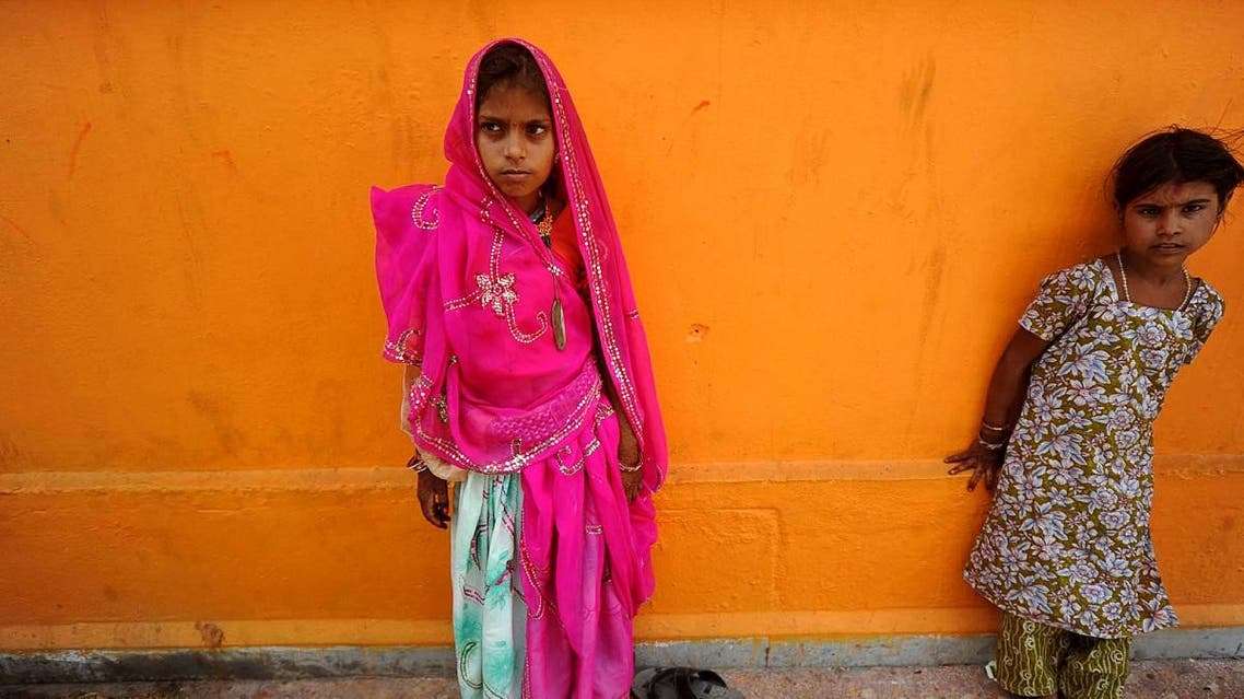 A newly married child bride, left, stands at a temple in Rajgarh, about 155 km from Bhopal, India. (File photo: AP)