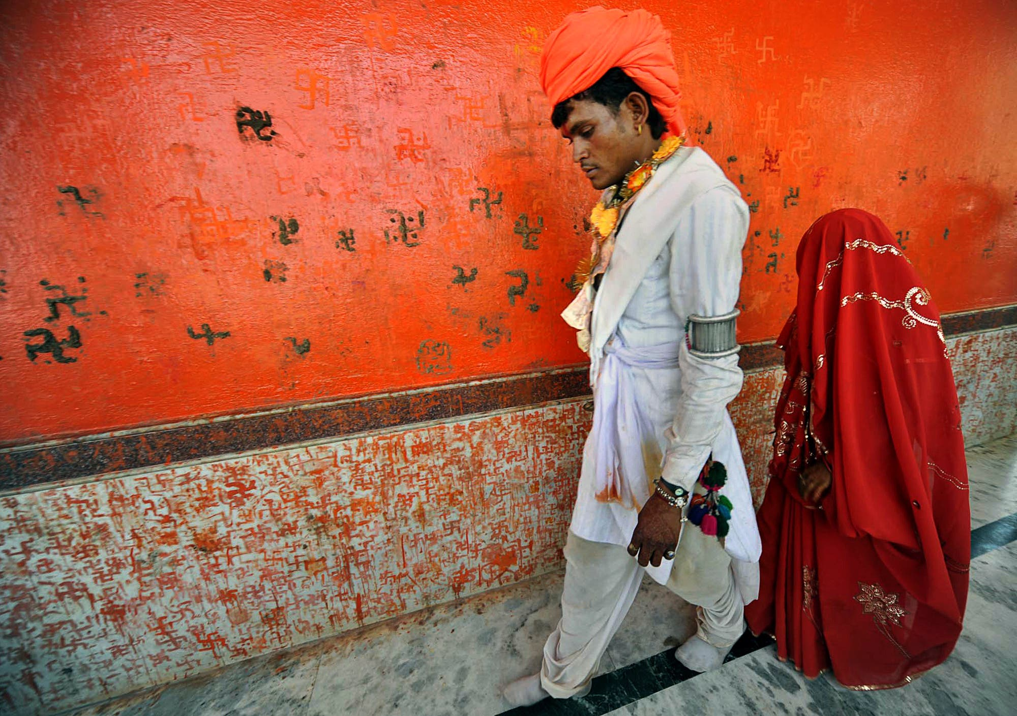 An under-age newly married couple who refused to be identified walk together after a mass marriage at Chachoda village in Rajgarh town. (AP)